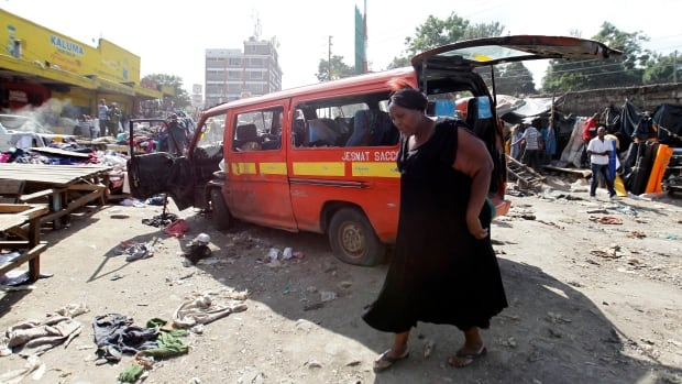 A woman walks near the scene of an explosion at open-air market in Kenya's capital Nairobi that killed four.
