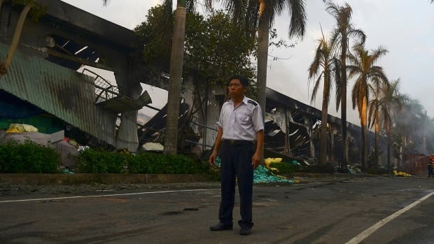 A security guard stands near a damaged Chinese-owned shoe factory in Vietnam's southern Binh Duong province earlier this week. Anti-China protests that started peacefully have ended in violence and vandalism, with 400 factories suspected of having links with China destroyed or damaged by mobs.