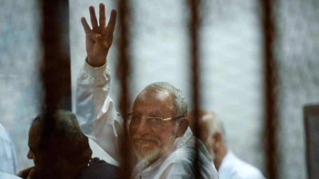 Leader of Egypt's Muslim Brotherhood Mohammed Badie sits inside a defendants cage as he raises his four fingers, a Rabaah al-Adawiya mosque symbol, where ousted leader Mohammed Morsi supporters had held a sit-in for weeks.