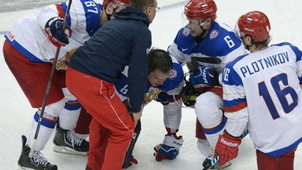Teammates help injured Russian forward Alexander Ovechkin during a game against Germany.