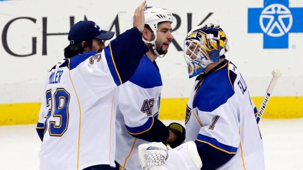 St. Louis Blues goalie Brian Elliott, right, celebrates a shutout in March with Ryan Miller, left, and defenceman Roman Polak.