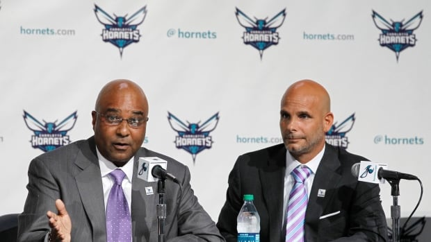 Charlotte Hornets president Fred Whitfield, left, and team marketing officer Pete Guelli, right, are shown Tuesday announcing the change.
