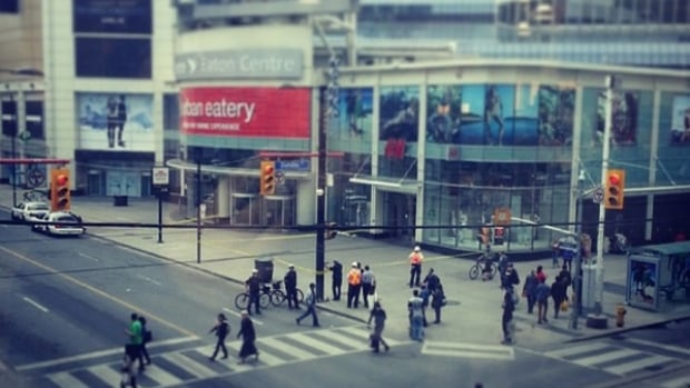 Police gather as a strip from a billboard fell down onto the corner of Yonge and Dundas streets, just outside the Eaton Centre.