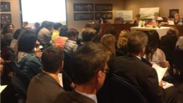 Trustees discussed the school closures in front of a meeting room packed full of parents.