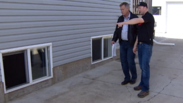 Spencer Bassett (right) shows the CBC's Mark Harvey the foundation of his house in Lloydminster.