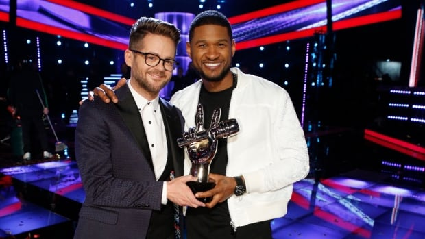 Josh Kaufman, left, poses with The Voice trophy and his coach Usher after being crowned winner of season six.