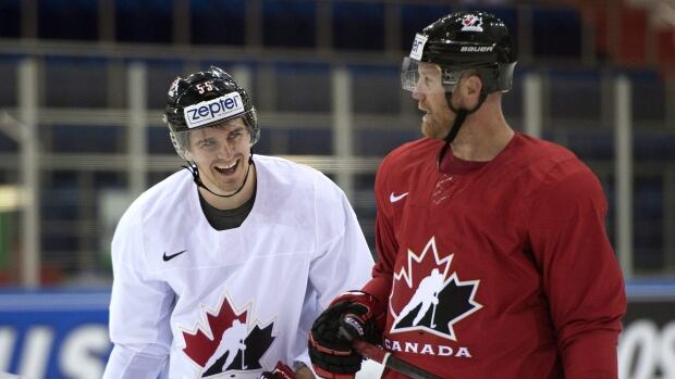 Team Canada forwards Mark Scheifele, left, and Jason Chimera chat during practice in Minsk on Wednesday.