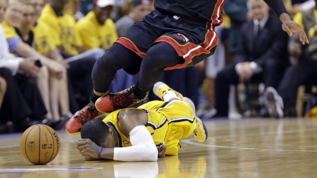 Indiana Pacers forward Paul George is on the deck as Miami's Dwyane Wade goes over in Tuesday's game.
