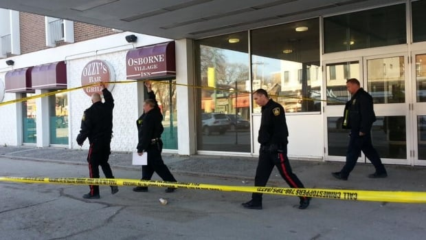 Members of the police identification unit come out of the Osborne Village Inn on Thursday.