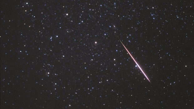 A meteor flashes across the constellation Andromeda during a past Perseid meteor shower. This year's peak coincides with a supermoon.