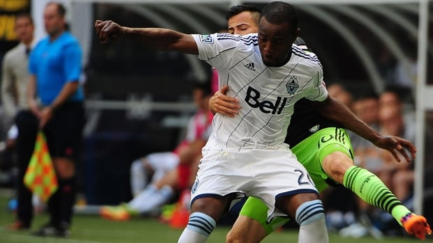 Nigel Reo-Coker (20) of the Whitecaps is grabbed from behind by Marco Pappa of the Sounders in a 2-2 draw on Saturday.