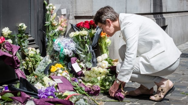 A woman lays flowers at the Jewish Museum in Brussels. French President Francois Hollande confirmed a suspect has been arrested and said France was determined to do all it could to stop radicalized youths from carrying out attacks.
