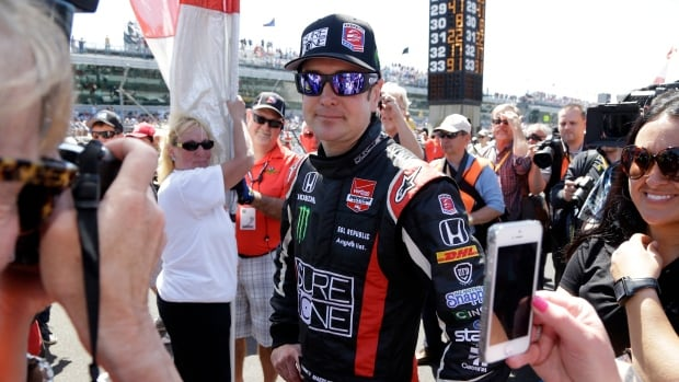 Kurt Busch is surrounded by fans as he stands on the starting grid before the start of the 98th running of the Indianapolis 500 IndyCar auto race at the Indianapolis Motor Speedway.