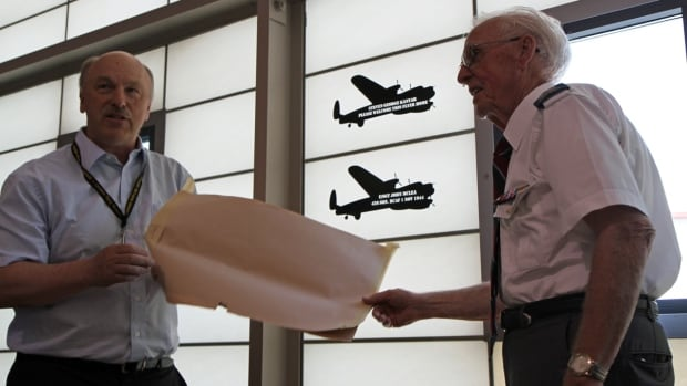Fraser Muir, right, and John McClenaghan unveil a glass plaque commemorating missing Hamilton airman John McLea at the Canadian Warplane Heritage Museum on Sunday afternoon.