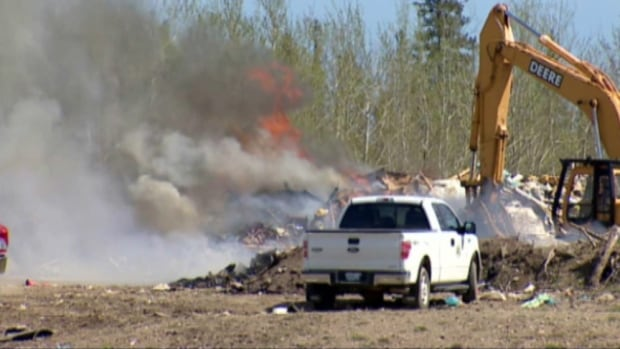 Firefighters take on a fire at the landfill in Hay River, N.W.T. on May 26. The fire got started when a garbage truck with a burning load arrived at the dump in the early afternoon.