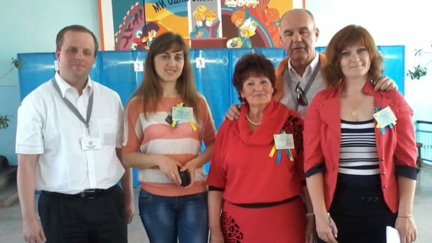 Tom Urbaniak (left) meets members of a Ukraine polling station in Ukraine.