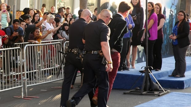 A fan is walked off the carpet in handcuffs at the world premiere of Maleficent at the El Capitan Theatre in L.A. The man allegedly rushed Brad Pitt, who was not hurt in the incident.