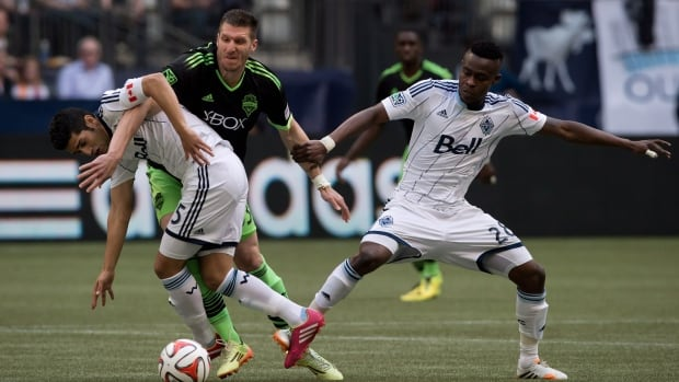 Vancouver teammates Matias Laba, left, and Gershon Koffie, right, battle Seattle's Kenny Cooper on May 24.