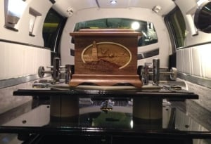 wooden urn in back of a hearse