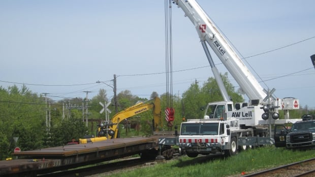 Work began Friday to remove sheets of steel from rail cars that derailed in New Glasgow Thursday evening.