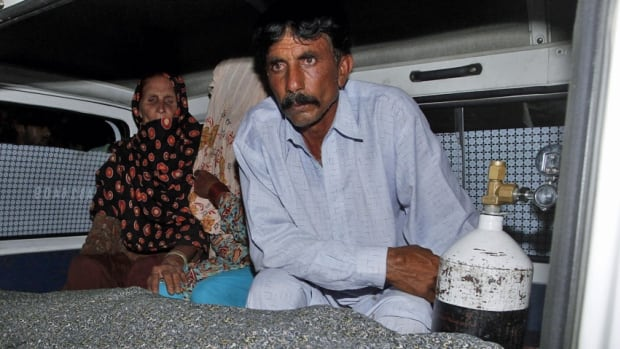 "Mohammad Iqbal sits next to his wife Farzana's body. She was stoned to death by her family outside one of Pakistan's top courts on Tuesday, in a so-called ""honour"" killing for marrying the man she loved, police said."