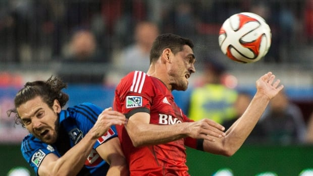 Toronto FC's Gilberto, right, heads the ball past Montreal Impact's Heath Pearce, left, during first half final of Wednesday's Amway Canadian Championship match.