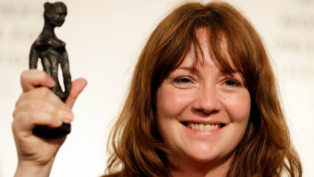 Eimear McBride hoists her Bessie trophy after winning the Baileys Women's Prize for Fiction for her debut novel A Girl is a Half-Formed Thing in London on Wednesday.