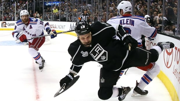 Kyle Clifford of the Kings is hit by Kevin Klein of the Rangers in Game 1 of Stanley Cup final at Staples Center on Wednesday.