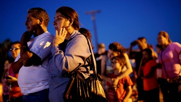 Residents watch investigators inspect the scene of a U.S. military jet crash in Imperial, California that damaged homes.