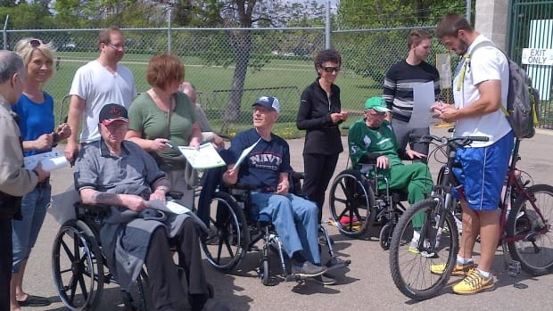 Saskatchewan Roughriders defensive end John Chick, seen on the far right, signs autographs for residents of the Sherbrooke Community Centre care home at training camp in Saskatoon on June 4, 2014.