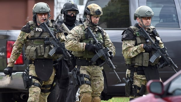 Emergency response officers check a residence in Moncton, N.B., in June 2014 during the search for the person who killed three RCMP officers and injured two others.