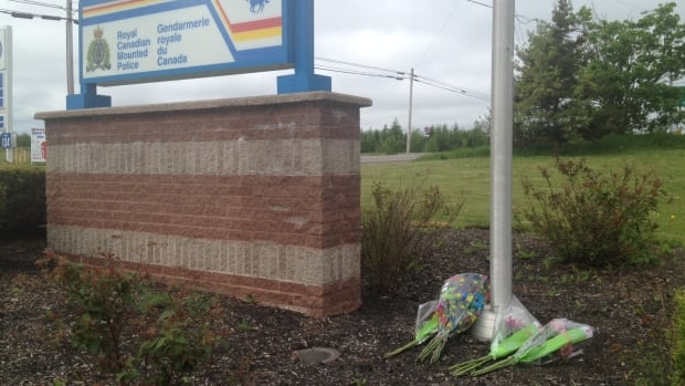 Bouquets of flowers rest underneath the flagpole at the RCMP detachment in