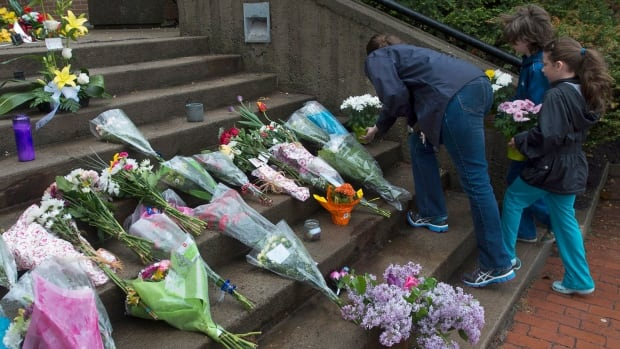 Flowers lie outside an RCMP detachment after one of the worst mass shootings in the RCMP's history, in Moncton, N.B., in June 2014. Three RCMP officers were killed and two injured. The shootings prompted lab tests by the RCMP to see whether semi-automatics can be temporarily made into full automatics with an improvised technique.
