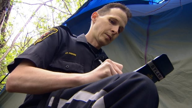 Calgary bylaw officer Jody St. Pierre checks on one of the homeless camps found in forested areas of Calgary.