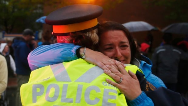 People wait in line to hug RCMP officers following a candlelight vigil in front of the Royal Canadian Mounted Police headquarters in Moncton, N.B. on June 6. Spouses of RCMP officers in Yellowknife have organized a community vigil Tuesday morning in memory of the officers who were killed last week in Moncton.