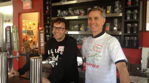 Village Brewery co-founder Jim Button, left, stands behind the bar at a stem cell and bone marrow swab-a-thon aimed at getting young men to register with Canada's donor database.
