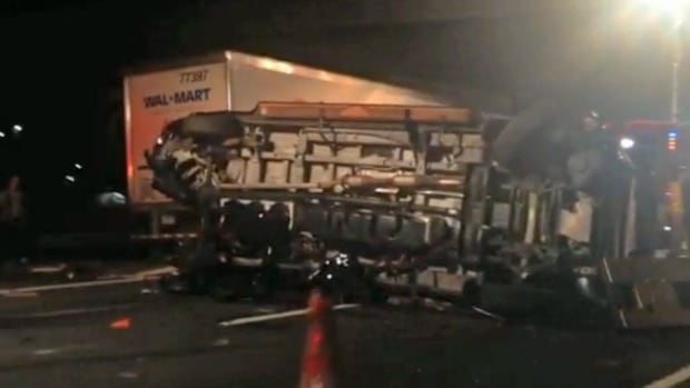 In this image from video, the limousine bus carrying Tracy Morgan and six other people lies on its side on the New Jersey Turnpike. State and federal officials continued their investigation of the six-vehicle crash.