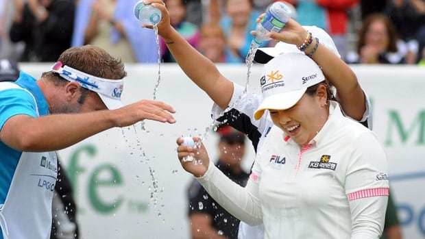 Lydia Ko of New Zealand pours water on Inbee Park, right, and her caddie after Park won the Manulife Financial LPGA Classic at the Grey Silo Golf Course in Waterloo, Ont., in June. Park tied the course record with a 10-under 61 in the final round for a three-shot win over Cristie Kerr.