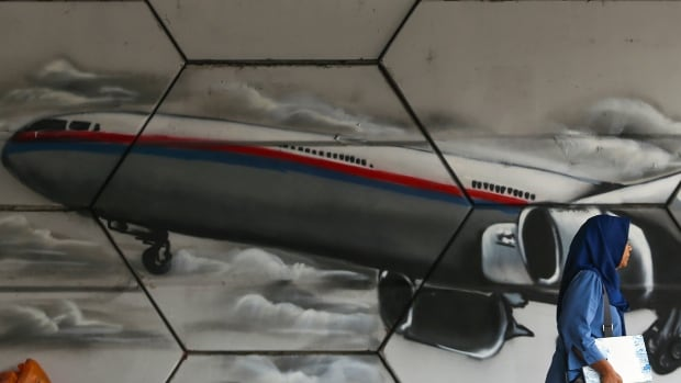 A woman walks past graffiti of the missing Malaysia Airlines Flight MH370 in Kuala Lumpur, Malaysia, in April. A team of experts says satellite transmissions from the plane show the flight ended somewhere in a large patch of the southern Indian Ocean.