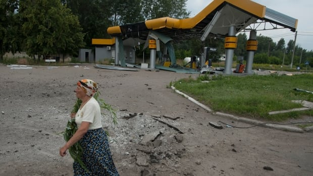 A woman walks past a gas station damaged by a mortar attack by Ukrainian government troops in Slovyansk, eastern Ukraine, on Monday. Several buildings have been damaged by shelling in an eastern Ukraine city controlled by pro-Russian separatists.