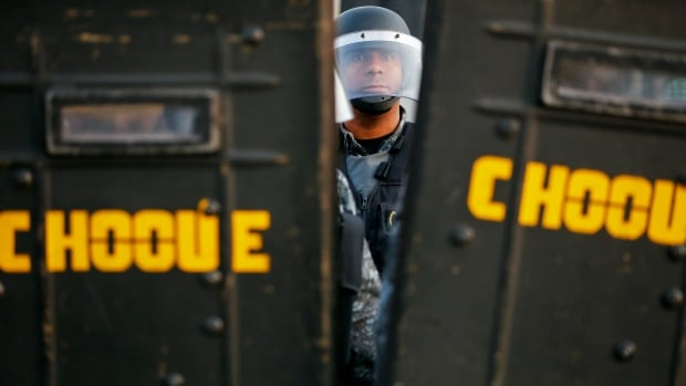 Policemen take position outside the closed entrance of a Sao Paulo subway station during the fifth day of metro worker's protest. The transit dispute is spreading chaos across Brazil's biggest city just days ahead of the opening match of the World Cup soccer tournament.