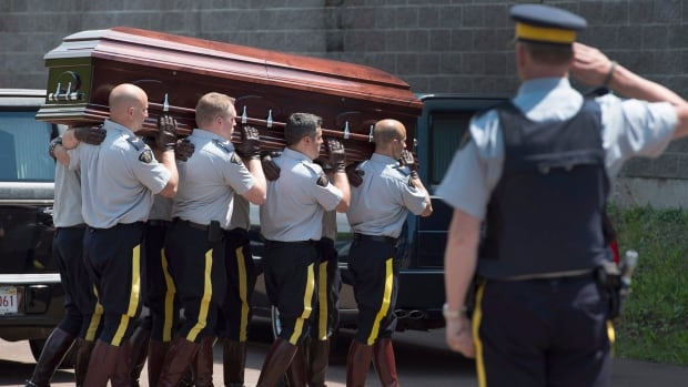 One of three caskets carrying RCMP officers killed on duty is carried into the Wesleyan Celebration Centre in Moncton, N.B., on Monday for a public visitation.