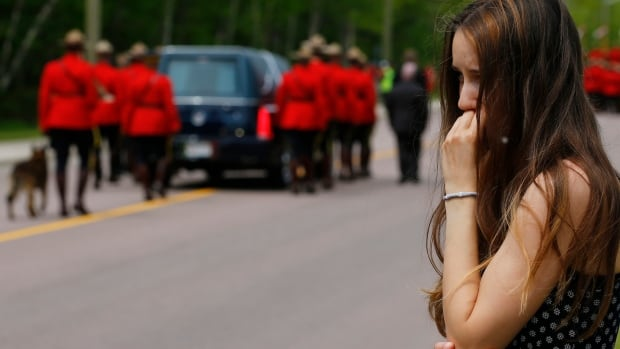 A woman watches the funeral procession for three RCMP officers killed.