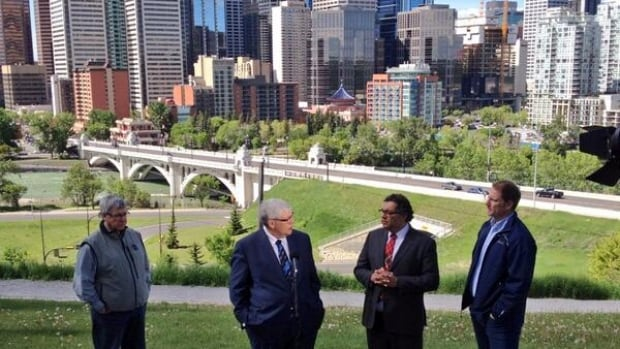 Calgary Mayor Naheed Nenshi stops for photos with Alberta's Premier Dave Hancock and MLAs Rick Fraser and Robin Campbell during a tour of Calgary neighbourhoods impacted by last year's flooding.