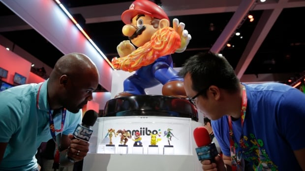 French television reporters look at Amiibo characters for Wii U at the Nintendo booth during the Electronic Entertainment Expo. The characters each contain a chip that stores their 'histories' will allow them to 'spring to life' within compatible games.