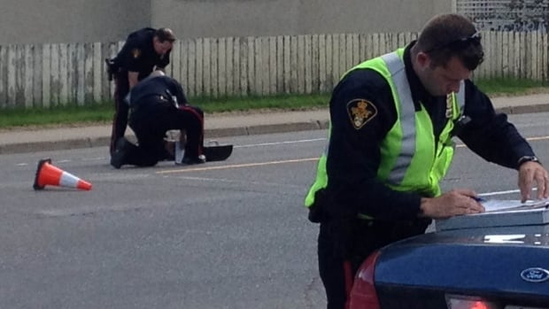 Police investigate a collision involving a vehicle and two pedestrians at a crosswalk.