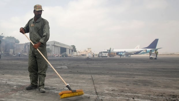 "A man clears debris from an airport tarmac after an attack earlier this month in Karachi, Pakistan. Two top government officials told Reuters that deadly drone strikes were carried out this week against the Taliban as a co-ordinated ""joint Pakistan-U.S. operation""."