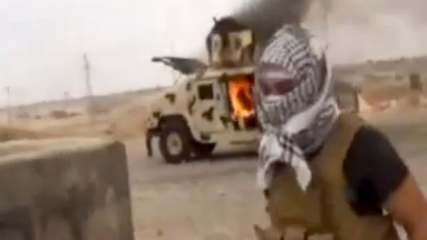 An Islamic State of Iraq and the Levant (ISIL) militant stands in front of a burning Iraqi Army Humvee in Tikrit, Iraq.
