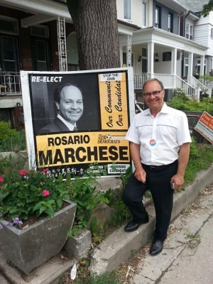 Rosario Marchese stands next to his sign