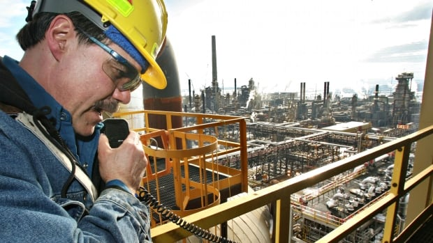 A worker communicates with another via radio at Syncrude's Mildred Lake Upgrader in Alberta's oilsands. A new report Thursday says shares in oilsands firms have been held down by foreign investment rules.